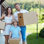 Smiling family with boxes by the house